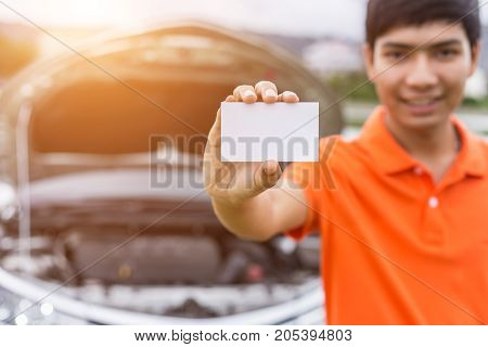 Aian Man Showing/holding Blank Of White Paper Or Business Card In Front Of Blur Damaged Car. For Car