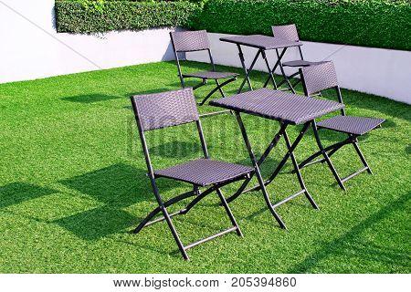 Black modern furniture on the green lawn.