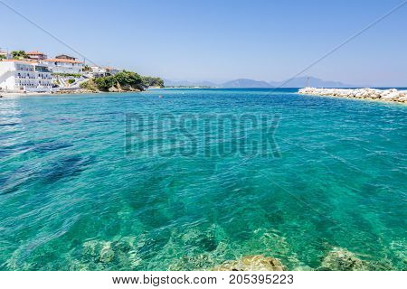 Rocky shallows with crystal clear water and beautiful settlement over blue sea.