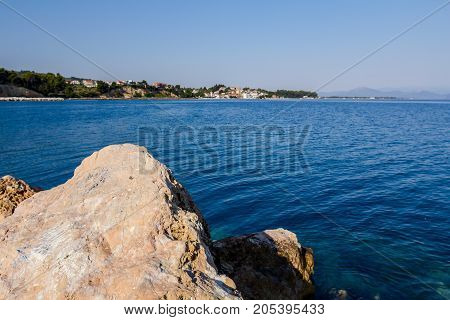 Rocky shore with boulder sticking out of water surface with beautiful settlement in the background