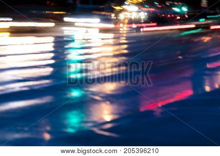 Blurred City Traffic Headlights Reflecting In Wet Road