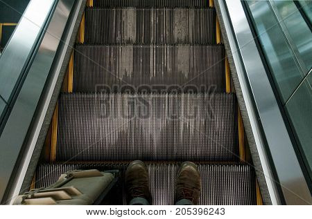 Top view of old boots on escalator steps.