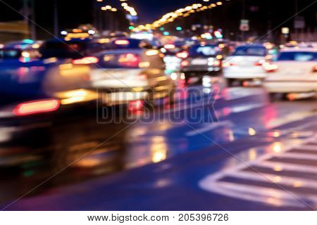 Blurred View Of Cars In Motion With Bright Headlights. City Road At Night.