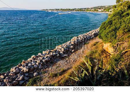 Stacked pile of stones along seashore against water erosion with green vegetation above.