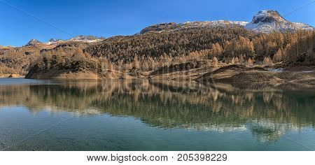 Lake of Devero in autumn season with high contrast shadow and sunny lights with snowy mountains and blue sky in the background - Piedmont Italy