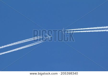 Two passengers airplanes are flying to each other in blue sky, telephoto shot
