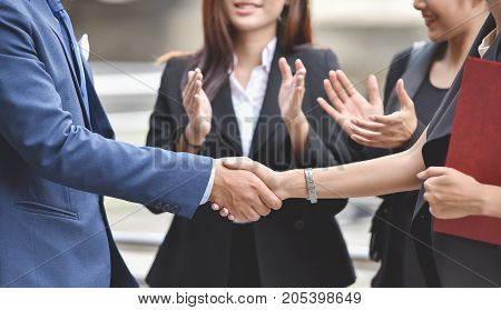 Happy businessman and businesswoman handshaking after negotiation with business people clap their hands background.