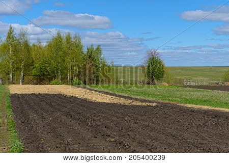 rustic plowed garden covered with straw on a sunny spring day