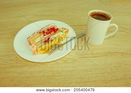 A cup of coffee and cake on wooden background. Fruit Cake with fresh red currant on the plate - Retro color