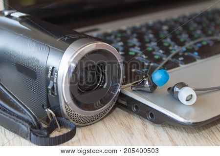 Set of modern computer devices - laptop headphones and camcorder close up