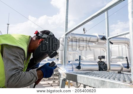 Welder Working At Heavy Industrial Construction Site