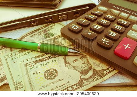 Stock market table analysis calculator and pen indicates research and analysis with cash. Money and a calculator - Retro color