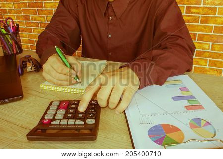 business accounting concept businesswoman and laptop with calculator on table working area. Businessman using a calculator to calculate the numbers - Retro color