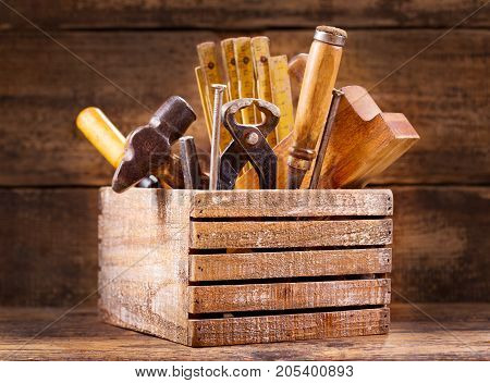 Old tools in a wooden box on wooden background