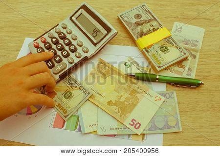 Hands using calculator and calculate money in home office. Counting money finance business - Retro color