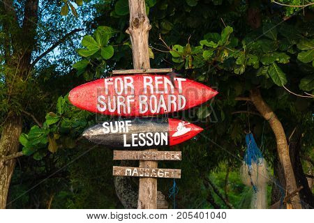 Bali Indonesia - May 12 2017: Sign board advertising surf lessons on Jimbaran beach a main popular balinese attraction famous for the clear blue water and sea food restaurants in Bali Indonesia.