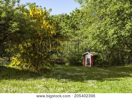 MARIEHAMN, ALAND ON JUNE 26. Outdoor view of the garden and playhouse at the old wooden Overnasstugan on June 26, 2017 in Mariehamn, Aland. Garden in bloom. Editorial use.