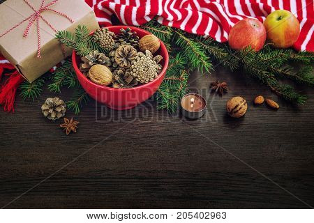 Christmas decoration - red bowl full of fir-cones gift box wrapped in kraft paper pine branches candle nuts anise apples and red and white striped winter scarf. Christmas theme. Dark wooden background.Copy space.