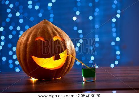 Shot of a Halloween pumpkin lantern on the table with a cocktail in a glass copyspace party festive celebration entertainment drinks autumn fun concept.