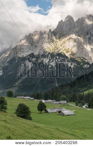 Rural View From The Swiss Alps, Around Grindelwald, With Rocky Peaks Shrouded In Clouds In The Backg