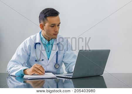 Asian young doctor using laptop computer for looking at patient information and hand holding pen at hospital isolated on gray background concept of medical technology innovation.