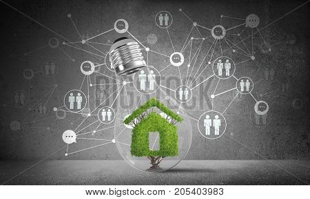 Lightbulb with green house sign inside placed against sketched social network system on grey wall. 3D rendering.