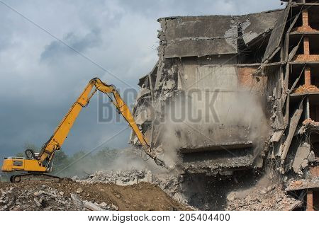 Remove a dangerous building in an urban area with a digger. Moment of collapse.