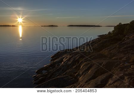 Sunset in the sea. Islands at the horizon.