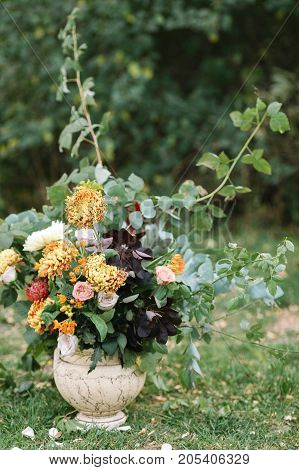 arranging, holidays, surprise concept. on the grass extremely beautiful wedding bouquet of such remarkable flowers as bright orange chrisantemums combined with delicate roses of different colours