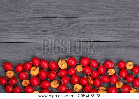 Hawthorn berry on a black wooden background with copy space for your text. Top view.