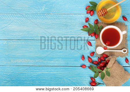 tea with rose hips and honey on blue wooden background with copy space for your text. Top view.