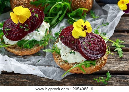 Rustic wholegrain buns with cottage cheese, rocket leaves, beetroot slices and edible viola flowers. Vegetarian food snack