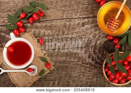 tea with rose hips and honey on old wooden background with copy space for your text. Top view.