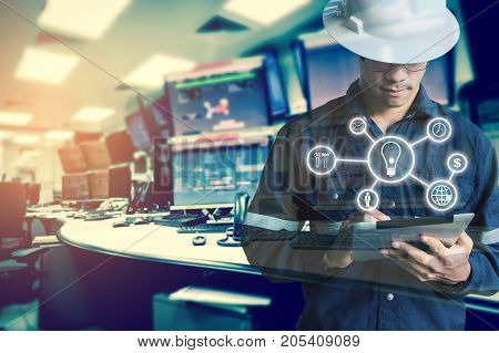 Double exposure of Engineer or Technician man with business industrial tool icons while using tablet with monitor of computers room for oil and gas industrial business concept.