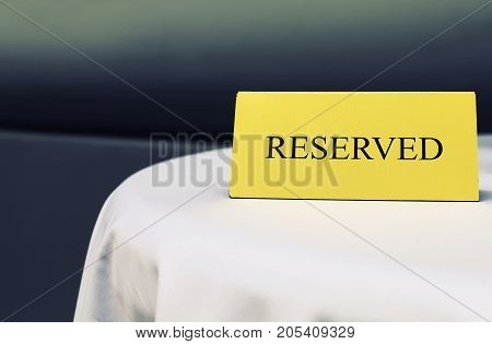 Reserved sign on the table in restaurant Close up