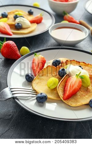 Homemade Pancakes with Blueberry, Strawberry, green Grape and honey syrup. served on plate.