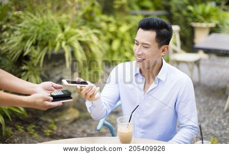 Man paying bill through smartphone using NFC technology in restaurant