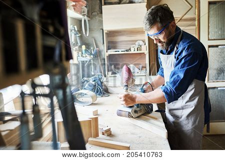 Portrait of mature bearded carpenter polishing piece of wood in workshop against window while making furniture