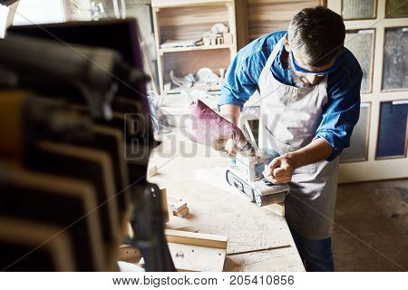 Portrait of skilled carpenter polishing piece of wood in workshop standing against window in sunlight and  making furniture
