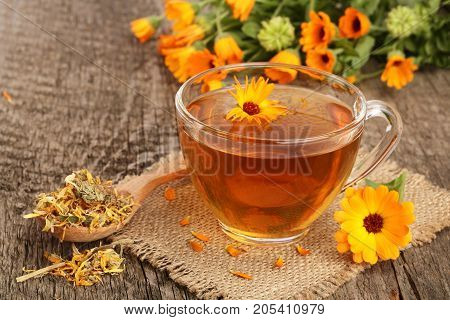 Calendula tea with fresh and dried flowers on old wooden background.