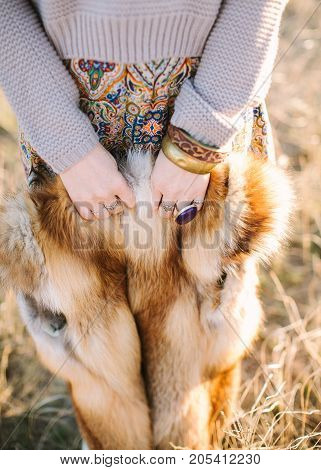 boho style, fall, freedom concept. charming girl dressed in skirt with ornaments of autumnal shades and smoky sweater holding red fox skin in small arms with original accessories
