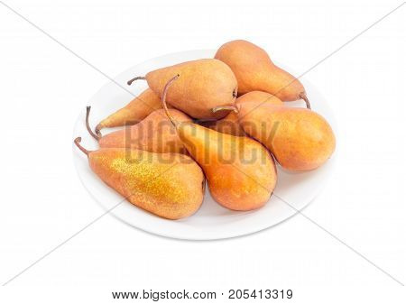 Several ripe yellow and light brown European pears of autumn variety Bere Bosc on a white dish on a white background