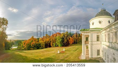 Facade of the 18th century neoclassical palace and large glade in front of him in autumn landscape park on the shore of a pond in national historic cultural preserve Kachanivka Ukraine