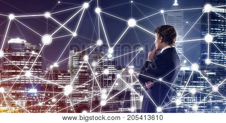 Thoughtful businessman against night cityscape looking at social connection media concept