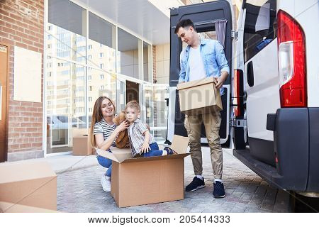Portrait of happy young family with little boy loading cardboard boxes into moving van outdoors