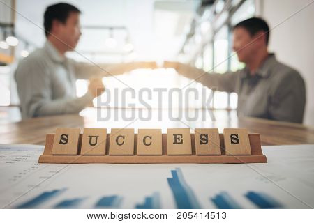 Business team meeting and discussion concept Success word on wood table in modern office.