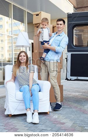 Portrait of happy young family sitting on armchair outdoors moving in new house, and posing for camera