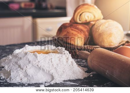 Raw dough for bread with ingredients on black background.