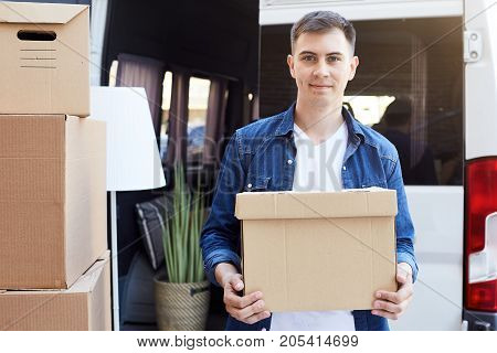 Portrait of smiling young man holding cardboard box and looking at camera while unloading moving van outdoors