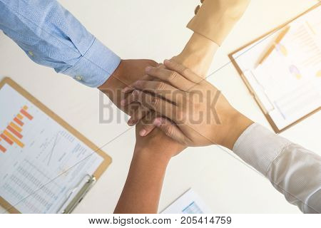 Close up top view of business people putting their hands together Group of colleagues with stack of hands teamwork and unity concept.